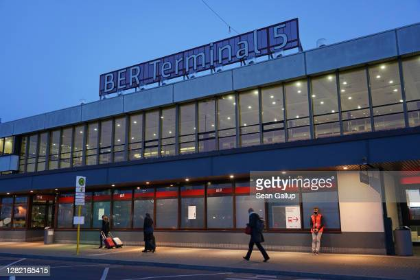 People walk in front of the main terminal of former Berlin Schoenefeld Airport on the day of its inauguration as Terminal 5 of the new Berlin...