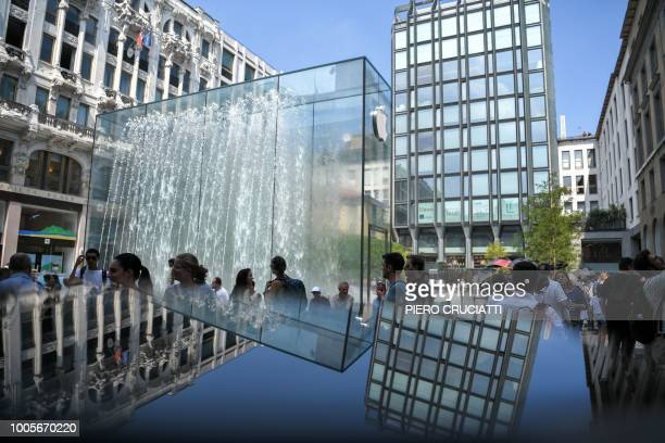 People walk in front of the new Apple Store Liberty the first Italian flagship store of Apple in Milan on July 26 2018