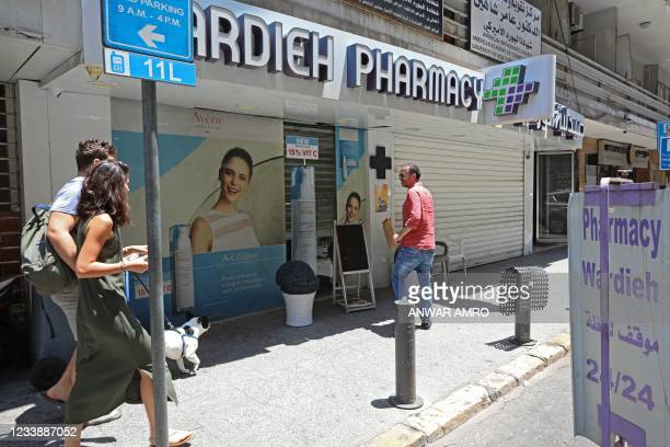 People walk in front of the shuttered door of a pharmacy in the Lebanese capital Beirut, during a nationwide strike of pharmacies to protest against...