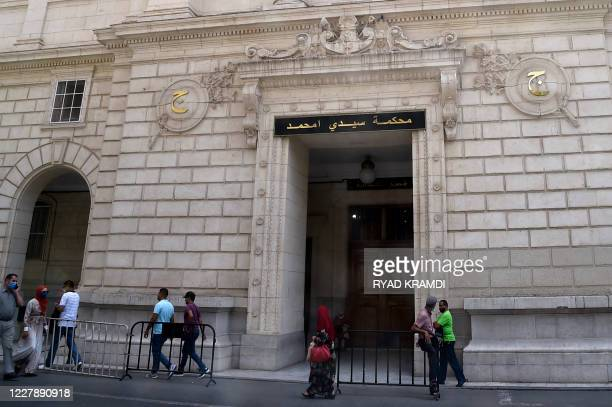 People walk in front of the Sidi Mohamed tribunal in the Algerian capital Algiers where the trial of detained journalist Khaled Drareni began, on...