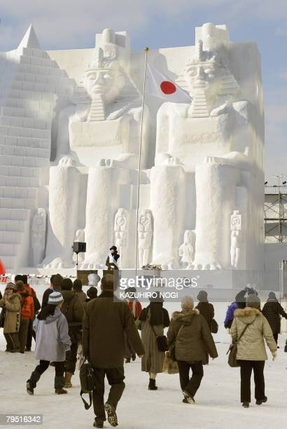 People walk in front of the snow sculpture of Egyptian statues at the Odori park in central Sapporo on February 5 2008 The annual Sapporo Snow...
