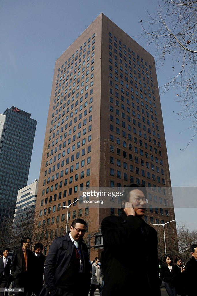 People walk in front of the YoungPoong Building, center, which houses the Deutsche Bank AG office, in Seoul, South Korea, on Thursday, Feb. 24, 2011. Deutsche Bank AG was given the heaviest penalty ever levied on a foreign securities firm in South Korea for triggering a Nov. 11 stock market rout that erased $26 billion of value. Photographer: Jean Chung/Bloomberg via Getty Images