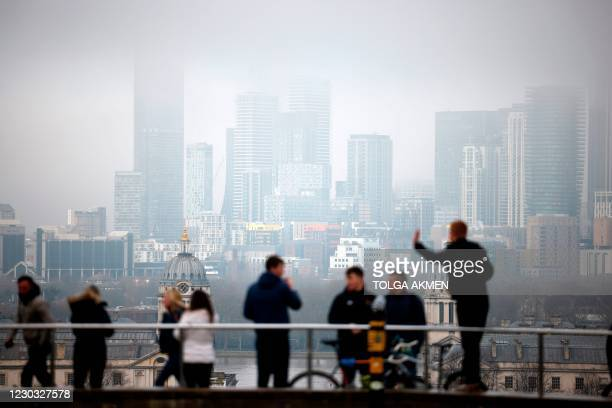People walk in Greenwich Park with the office buildings of the Canary Wharf financial district in the background in London on the bank holiday,...