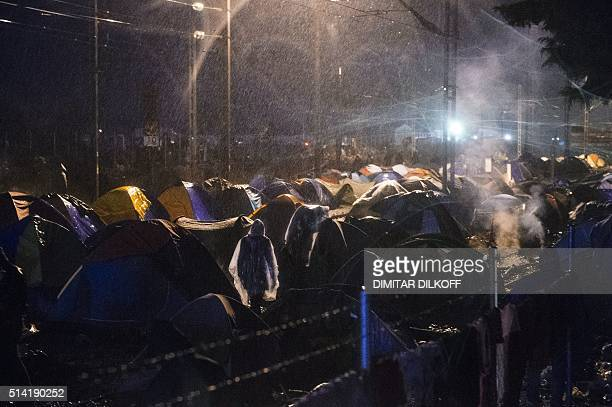 People walk in heavy rain among tents of a makeshift camp at the GreekMacedonian border near the Greek village of Idomeni where thousands of refugees...