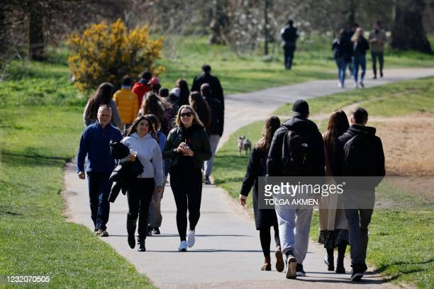 People walk in Hyde Park in central London on April 2, 2021 as life continues following an easing of the coronavirus restrictions to allow people...