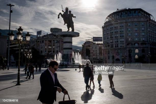 People walk in Macedonia Square in front of a statue of Alexander the Great on September 28, 2018 in Skopje, Macedonia. Macedonians will go to the...