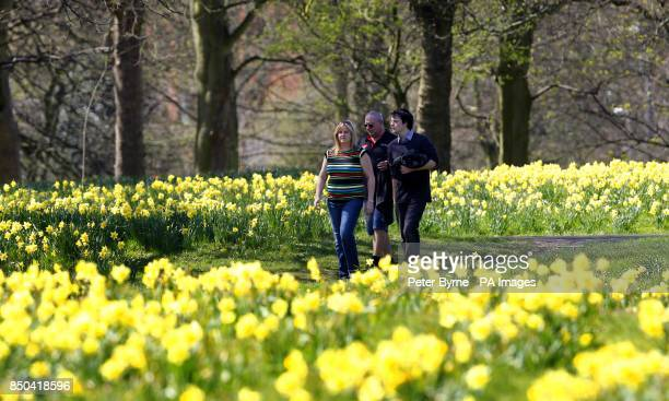 People walk in Sefton Park Liverpool during the warm spring weather