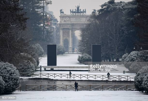 People walk in Sempione garden after snowfall in Milan on March 1 2018 Fresh heavy snowfalls and icy blizzards were expected to lash Europe on March...