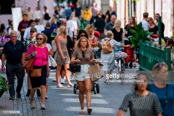 People walk in Stockholm on July 27 during the novel coronavirus / COVID-19 pandemic. - Although the use of face masks has become taken for granted...