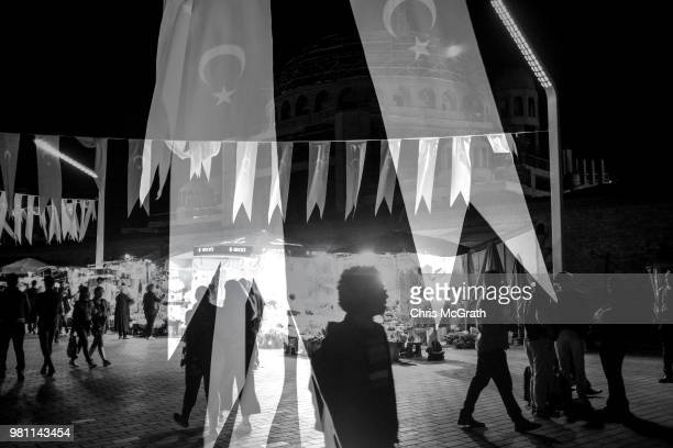 People walk in Taksim square overlayed by Turkish flags on April 23 2018 in Istanbul Turkey With Turkey being just days away from the most important...