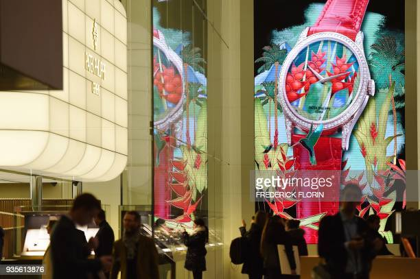 People walk in the alleys during the press day of the Baselworld watch and jewellery fair on March 21 2018 in Basel on the eve of its opening / AFP...