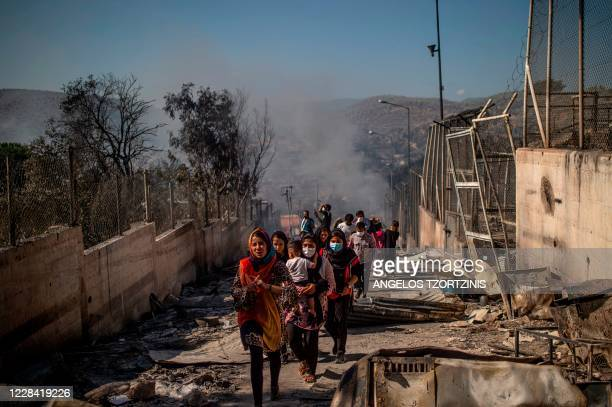 People walk in the burnt camp of Moria on the island of Lesbos after a major fire broke out, on September 9, 2020. - Thousands of asylum seekers on...