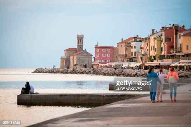 People walk in the Cape Madona area in the coastal town of Piran Slovenia on May 6 2018