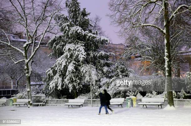 People walk in the Champs de Mars garden covered by snow near the Eiffel Tower on February 7 2018 in Paris France After exceptionally heavy snow last...