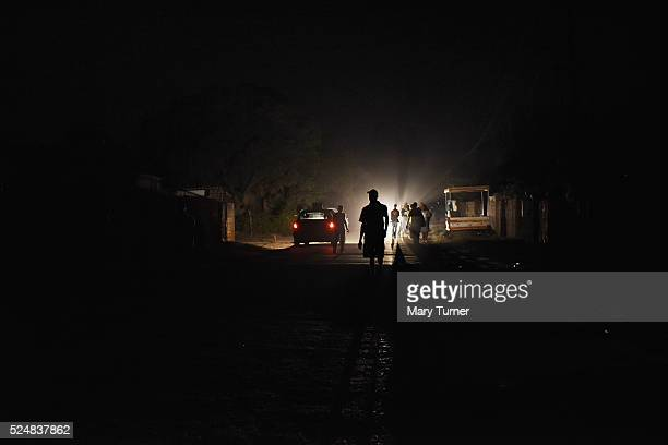 People walk in the darkness illuminated by car headlights as there is no electricty until late at night due in Chitungwiza Zimbabwe on October 8th...
