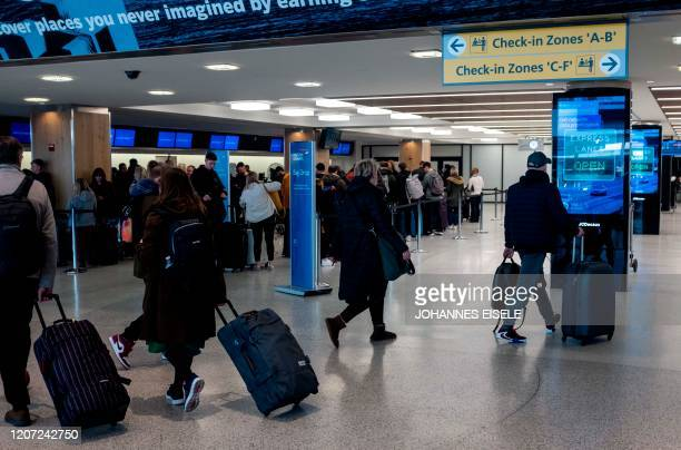 People walk in the departure hall of Terminal 7 at JFK airport on March 15, 2020 in New York City. - Chaos gripped major US airports Sunday as...
