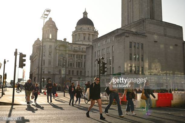 People walk in the early evening sunshine on the Pier Head in Liverpool, north-west England on September 18, 2020 after the British government...