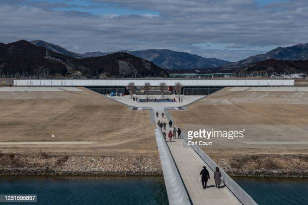 People walk in the grounds of the Iwate Tsunami Memorial Museum on March 8, 2021 in Rikuzentakata, Japan. In ceremonies that are expected to be...