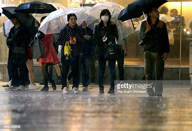 People walk in the heavy rain on April 6 2013 in Tokyo Japan A strong low pressure triggers torrential rain across Japan the rain falls cherry...
