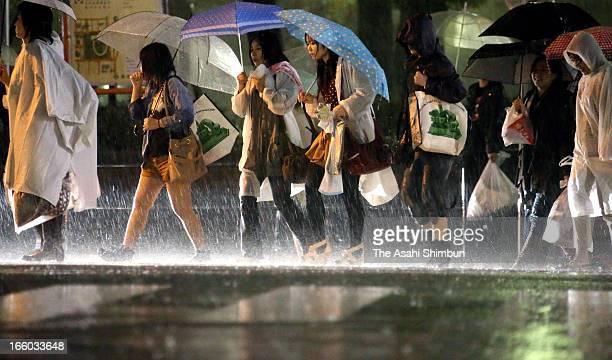People walk in the heavy rain on April 6 2013 in Yokohama Kanagawa Japan A strong low pressure triggers torrential rain across Japan the rain falls...