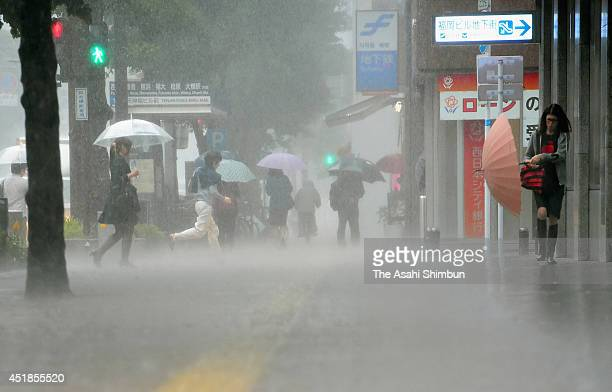 People walk in the heavy rain on July 7 2014 in Fukuoka Japan Torrential rain triggered by an active rain front hit Northern Kyushu area