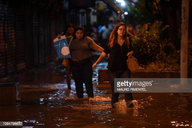 People walk in the inundated streets of the Botafogo neighborhood after a strong rain flooded multiple areas of the city of Rio de Janeiro Brazil on...