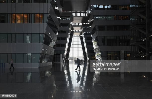 People walk in the main hall at the new NATO headquarters during a press tour of the facilities as NATO is moving from its old headquarters to the...