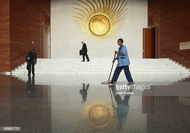 People walk in the main lobby under a fiery sculpture showing the African continent at the headquarters of the African Union on March 18 2013 in...