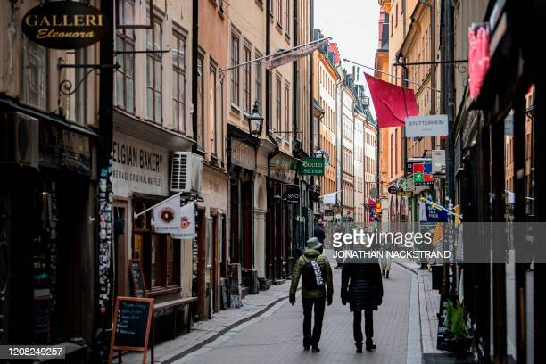 People walk in the main street of the old town in Stockholm, Sweden, while the rest of Europe is in lockdown in a bid to curb the spread of the new...