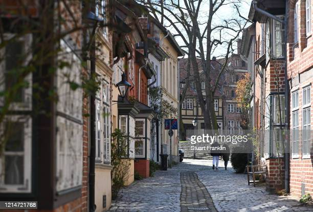 People walk in the medieval town of Luneburg on March 25, 2020 in Luneburg, Germany. Everyday life in Luneburg, Germany has become fundamentally...