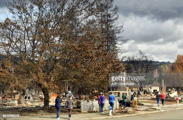 People walk in the neighborhood of Coffey Park to view burned homes in Santa Rosa California on October 20 2017 Residents were being allowed on...