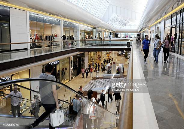 People walk in the new 'Les Terrasses du Port' shopping centre in Marseille southern France on May 23 on the eve of its opening to the public 'Les...