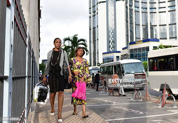 People walk in the Plateau business district of Abidjan on May 3 2016 / AFP / ISSOUF SANOGO