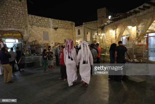People walk in the popular Souq Waqif market in the Qatari capital Doha on June 7 2017 Saudi Arabia Egypt the UAE and Bahrain announced on June 5...