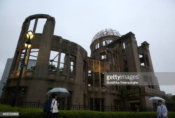 People walk in the rain in front of a Atomic Bomb Dome at the Hiroshima Peace Memorial Park on the day of the 69th anniversary of the atomic bombing...