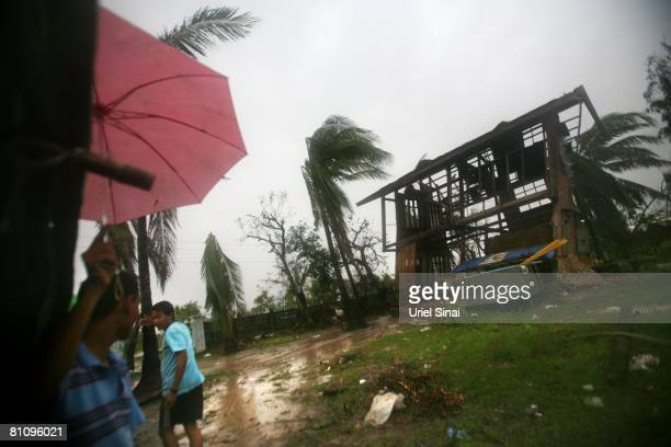 People walk in the rain outside the remains of their house on May 15 in a village on the outskirts of Yangon Myanmar It has been estimated that more...