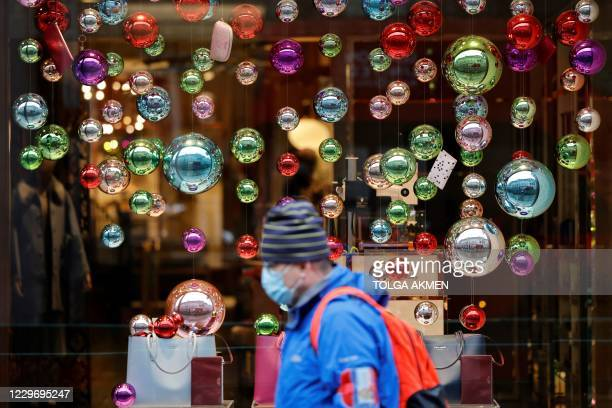 People walk in the rain past Christmas decorations in central London on November 20 as life under a second lockdown continues in England. - The...