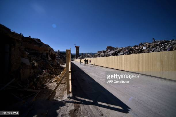 People walk in the remains of Amatrice on August 23, 2017 a year after a deadly earthquake left nearly 300 people dead and destroyed the small town....