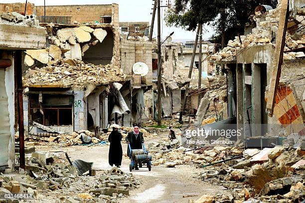 People walk in the rubble on January 9 2017 in Aleppo Syria Bashar alAssad administration backed by Russia recaptured the area in eastern Aleppo...