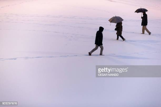 People walk in the snow after a heavy snowfall in Burgos northern Spain on February 28 2018 School was cancelled across swathes of Europe as a blast...