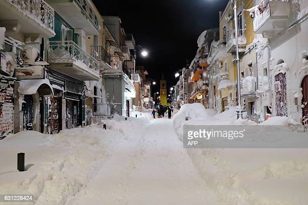 People walk in the snow in a street of Santeramo in Colle on January 7 2017 after snowfall near Bari in the Puglia region in the south of Italy A...