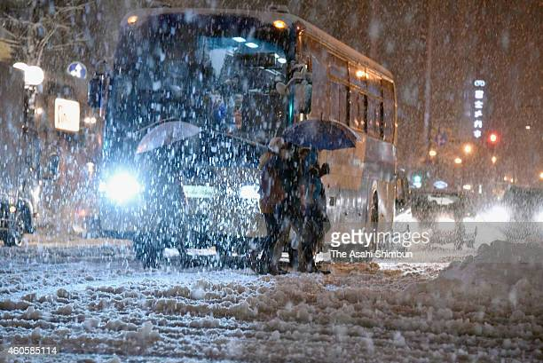 People walk in the snow on December 17 2014 in Sapporo Hokkaido Japan A rapid development of the wintry low atmospheric pressure cause blizzard in...