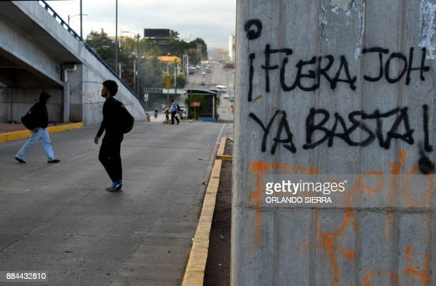 People walk in the street a day after the Honduran government declared a state of emergency and imposed a 10day curfew in an attempt to stop violent...