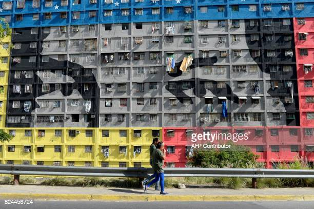 TOPSHOT People walk in the street during elections for a Constituent Assembly in Caracas on July 30 2017 Polls opened in Venezuela on Sunday for the...