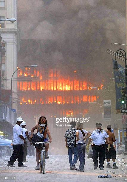 People walk in the street in the area where the World Trade Center buildings collapsed September 11 2001 after two airplanes slammed into the twin...