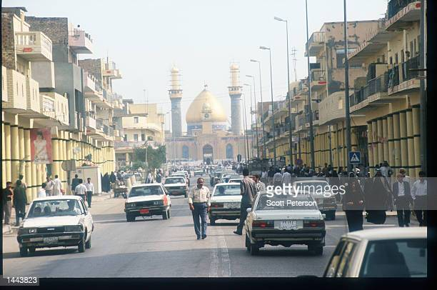 People walk in the street May 2 1997 in Tikrit Iraq Since the invasion of Kuwait by Iraq in August 1990 embargoes have prevented most of the...