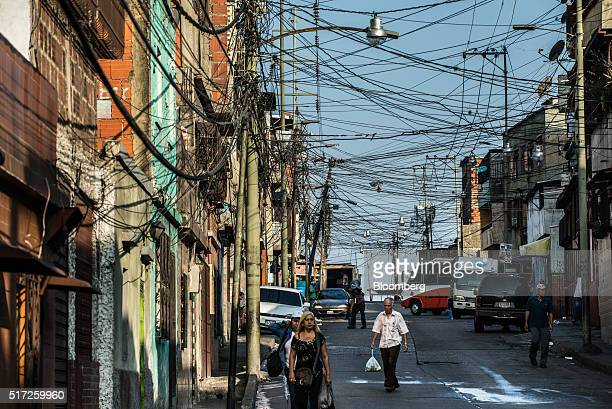 People walk in the street under improvised electrical wiring in a slum regularly subject to statemandated electricity rationing in Caracas Venezuela...