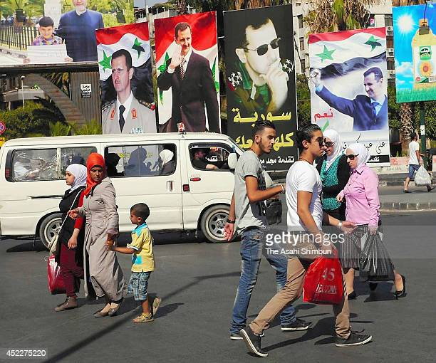 People walk in the street where posters of Bashar alAssad hang on July 15 2014 in Damascus Syria