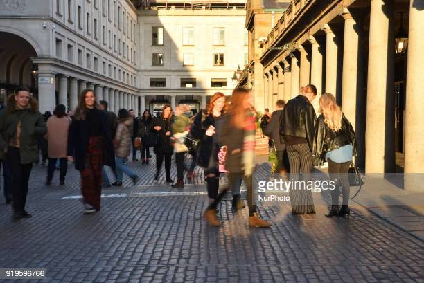 People walk in the streets of the historic District pf Covent Garden as the sun sets London on February 17 2018