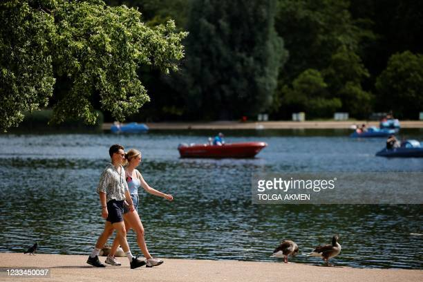 People walk in the sunshine in past the boating lake in Hyde Park in London on June 14, 2021. - Britain was on Monday widely expected to delay the...